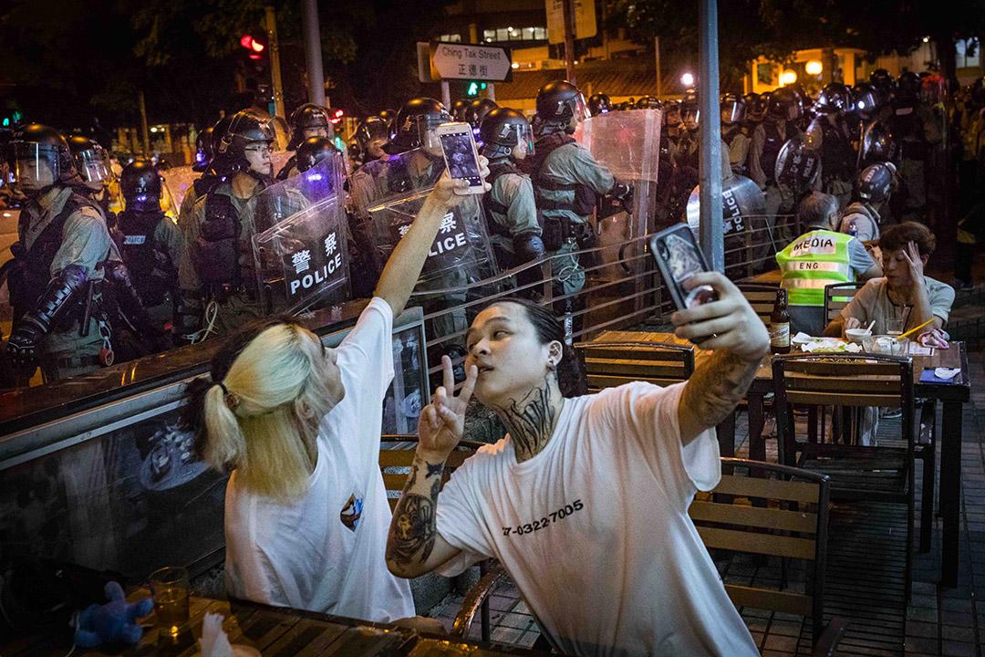 2019年8月4日,防暴警察在黃大仙清場,期間在大排檔吃飯的市民自拍。