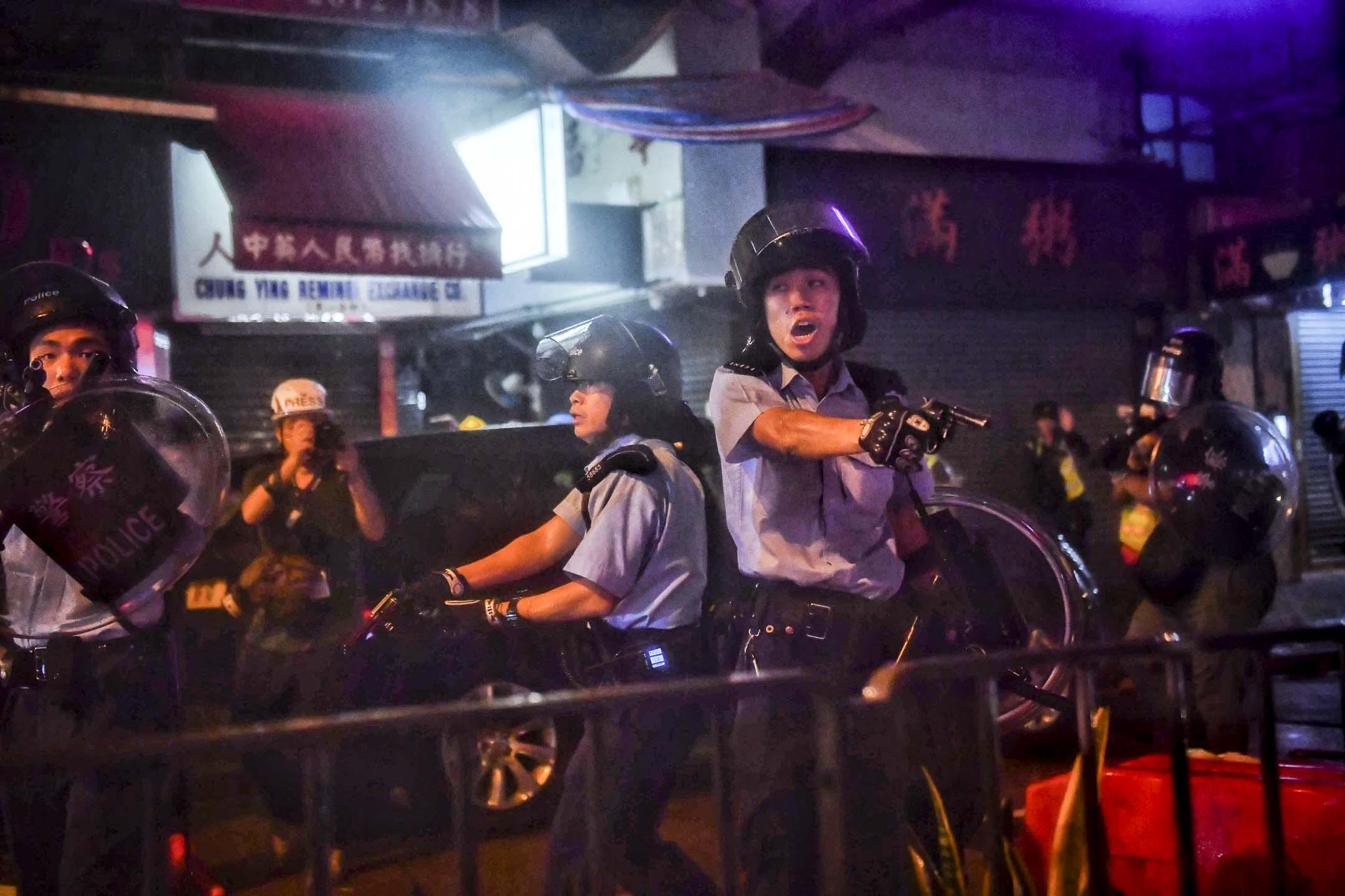荃灣有警員被受到群眾攻擊的情況下開槍示警,並且以槍指向示威者及記者。 攝:Lillian Suwanrumpa/AFP/Getty Images