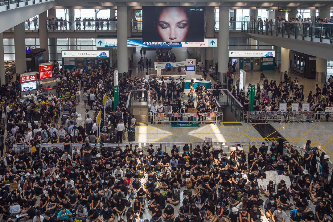 3時未到,身穿黑衣的示威者已經坐滿接機大堂,人數明顯比前兩次機場集會更多。