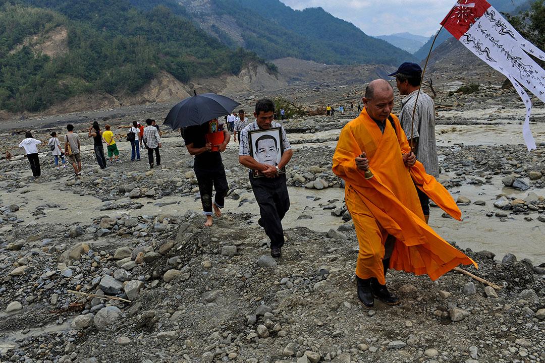 2009年8月15日,一名僧人在高雄縣遭遇破壞的小林村祭祀,其中有人帶著親人的肖像。