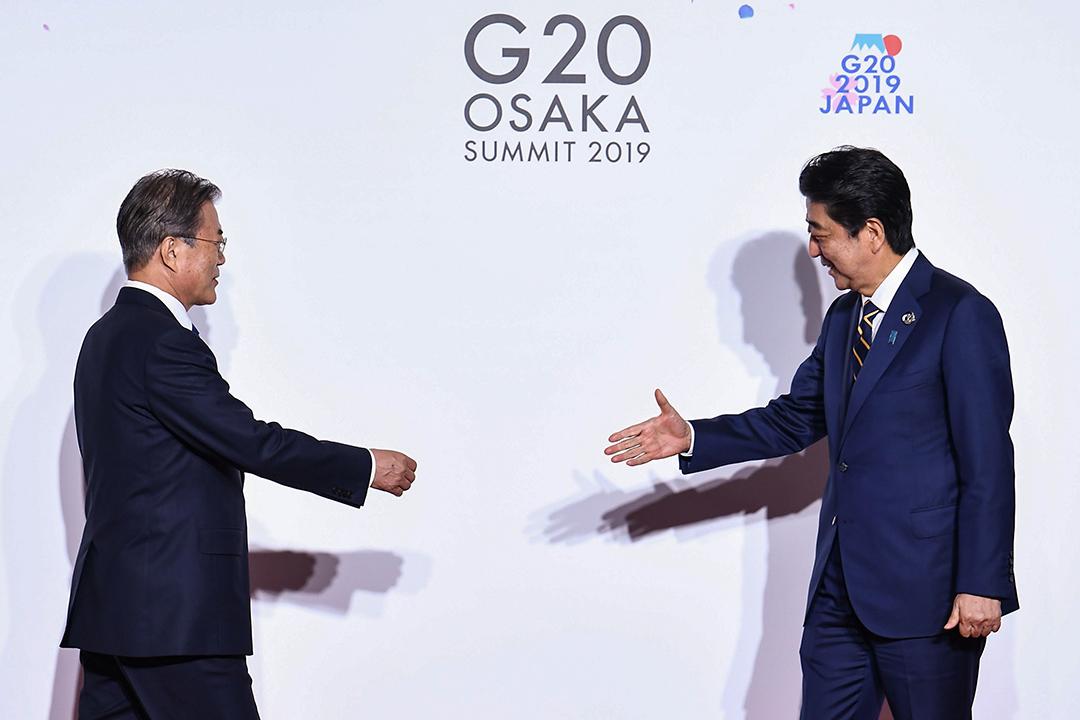 2019年6月28日在大阪舉行的G20峰會上,韓國總統文在寅與日本首相安倍晉三合照。