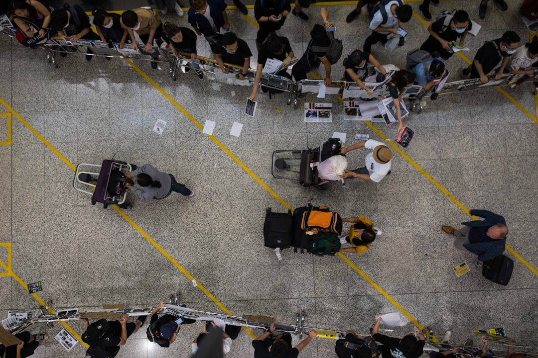 港人在機場發起「警察還眼」集會,機場方面以鐵馬圍起供旅客離開的通道。