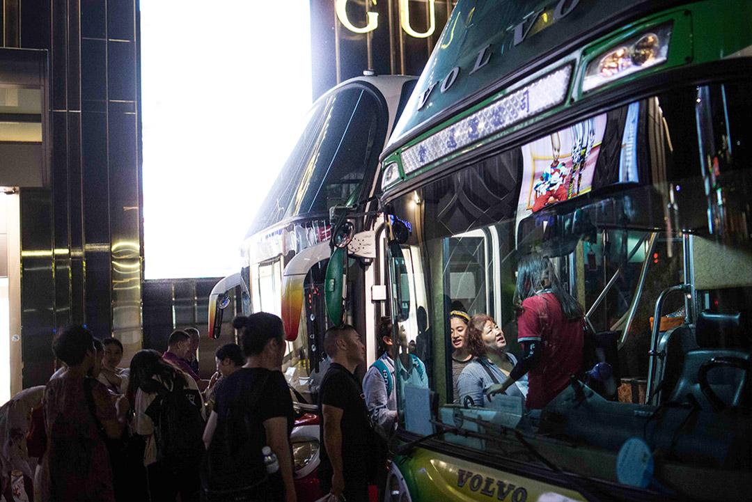 一群中國旅客在金門的商場外乘搭旅遊巴士。