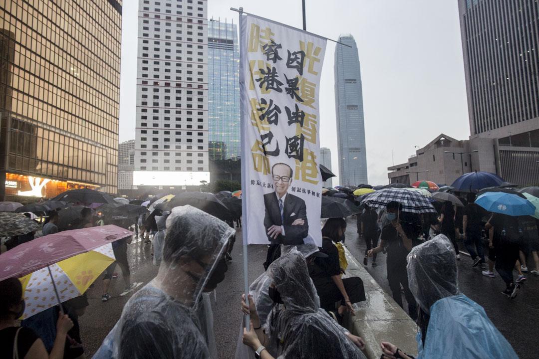 8月18日,傍晚7點左右,示威者手舉带有李嘉誠形象和「因果由國,容港治己」的標牌。