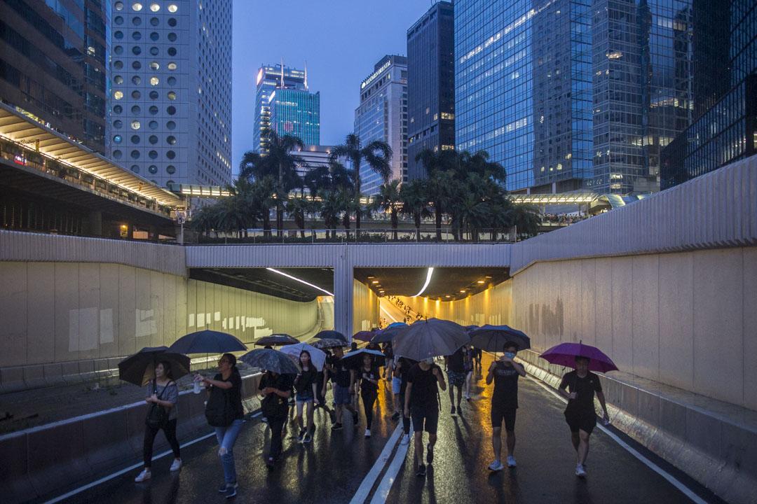 8月18日,入夜時分,一班黑衣示威者穿過隧道。