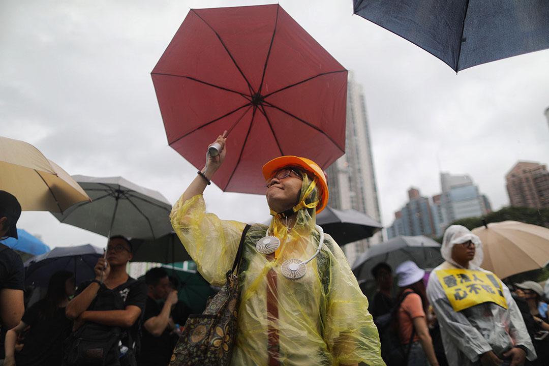 8月18日,傍晚6時許,一名示威者手持雨傘、頭戴頭盔走在街道上。