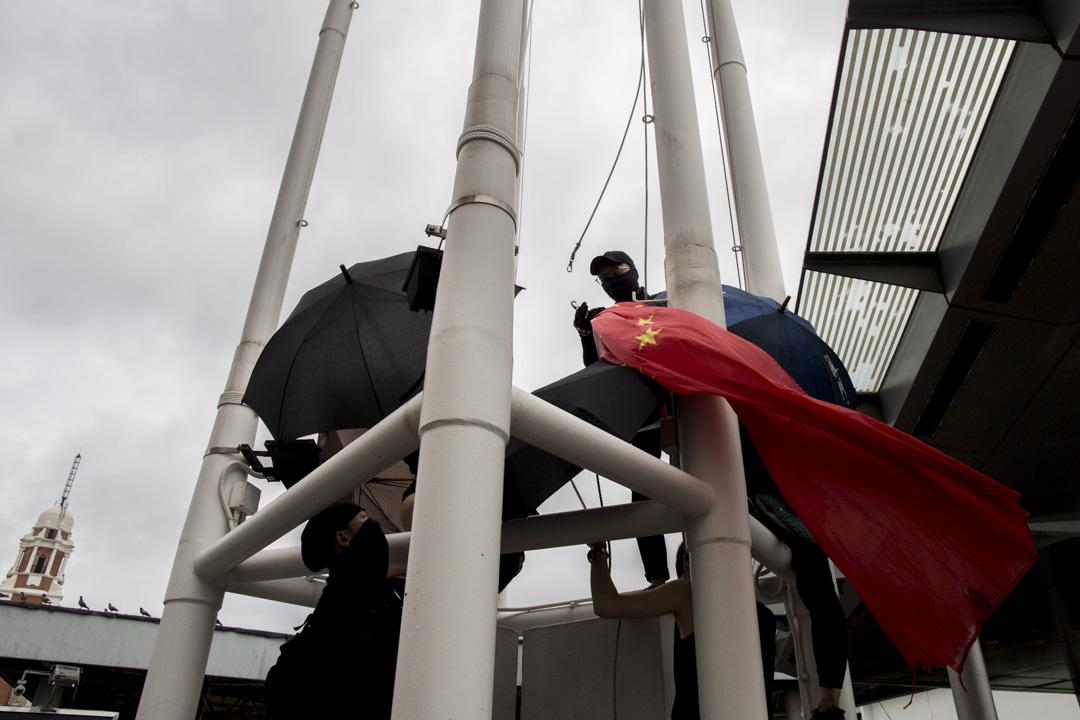 2019年8月3日,遊行人士到尖沙咀碼頭旁的五支旗杆、卸下國旗並拋到海裡。