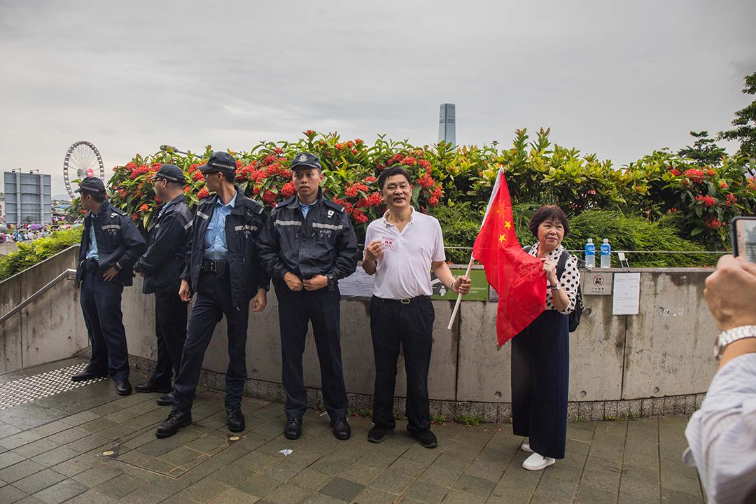2019年8月17日,「守護香港大聯盟」在金鐘政府總部旁的添馬公園舉辦「反暴力、救香港」集會,參與者與警察合照。
