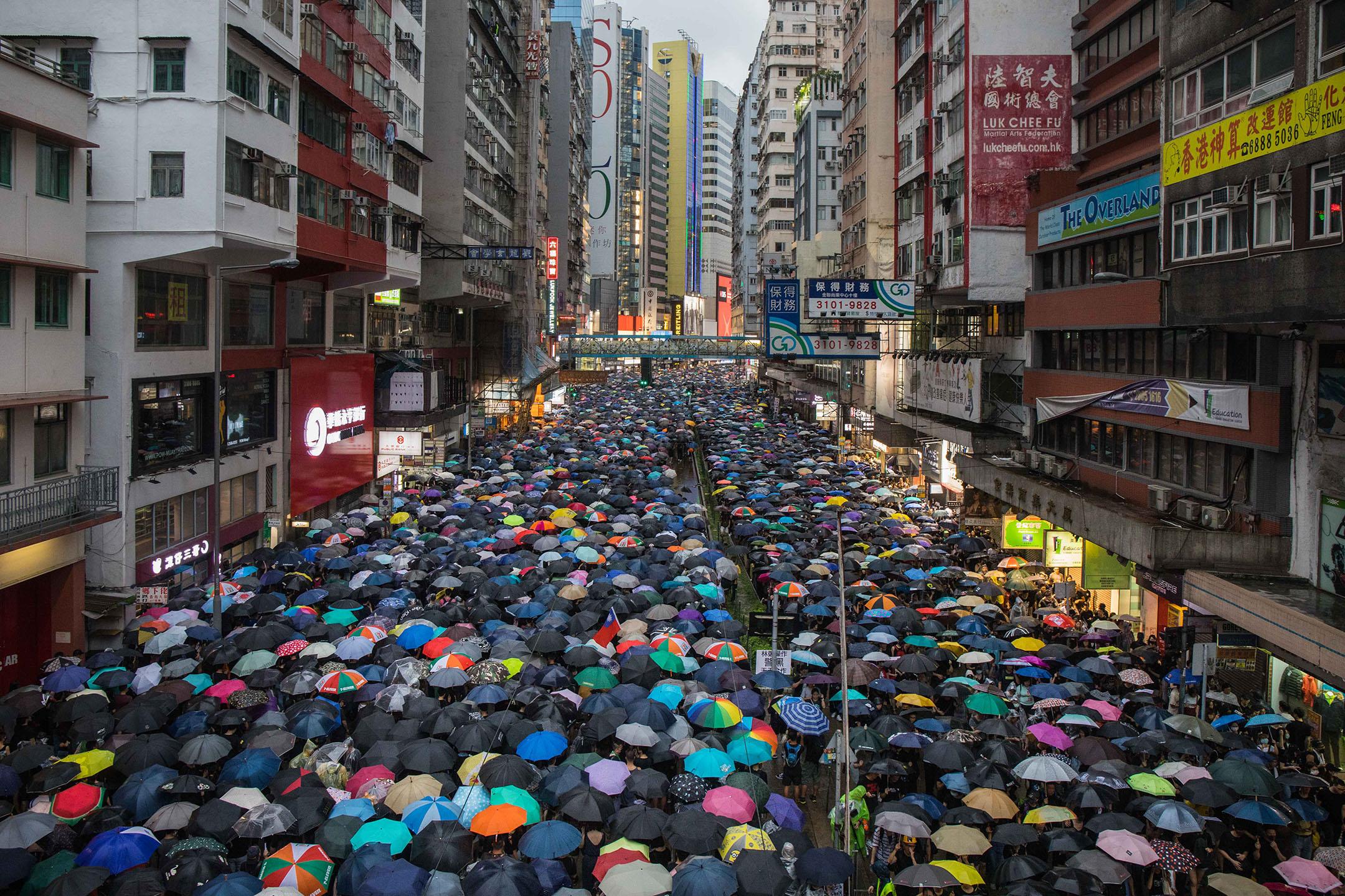 8月18日,傍晚六時許銅鑼灣,華燈初上,示威者撐傘走在城市间。
