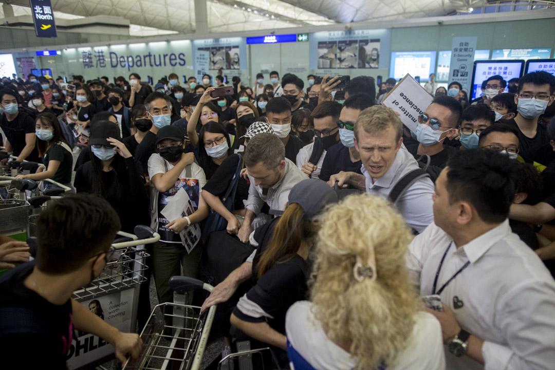 外藉旅客希望穿過示威人群進入禁區。