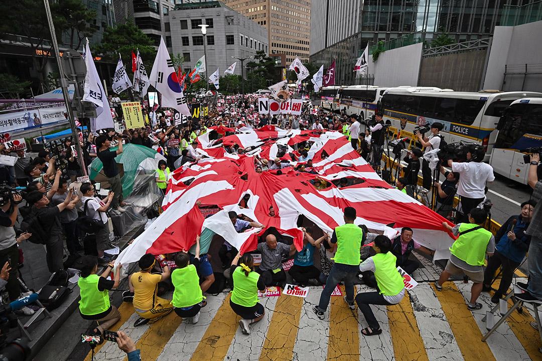 2019年7月20日,韓國示威者在日本駐首爾大使館附近譴責日本對南韓實施貿易限制的集會,期間撕毀了日本太陽旗。 攝:Jung Yeon Je/AFP via Getty Images