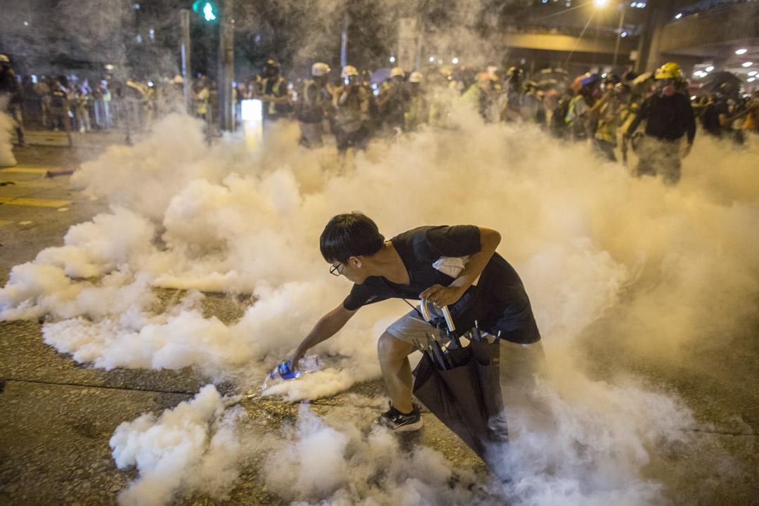 2019年8月3日,黃大仙地鐵站外有大批未戴口罩、裝備的市民包圍驅趕警方,最後引起警察清場,其中有全無裝備的市民以水淋熄催淚彈。 攝:林振東/端傳媒