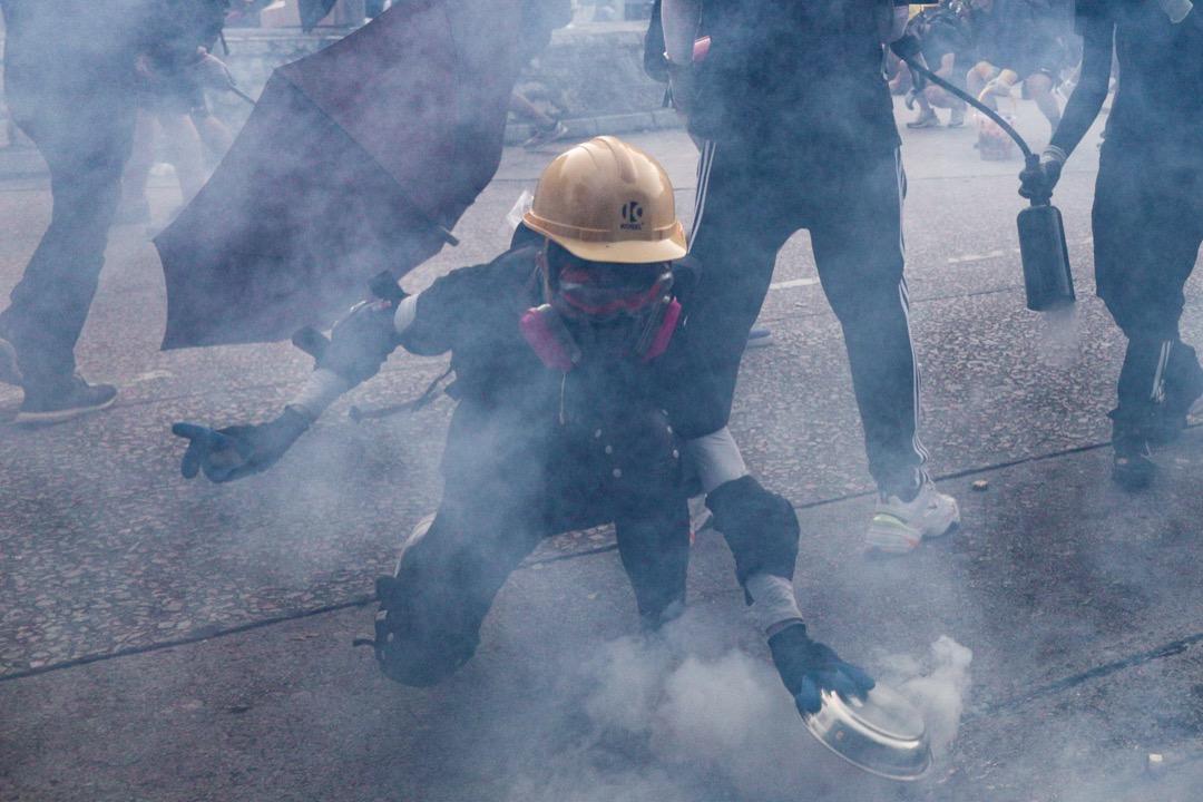 一名戴上配置60926濾罐的面罩的示威者用鋁碟撲滅一枚催淚彈。
