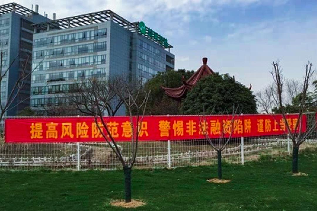 錢寶網南京總部的外圍欄上,當地警方懸掛了警示橫幅。