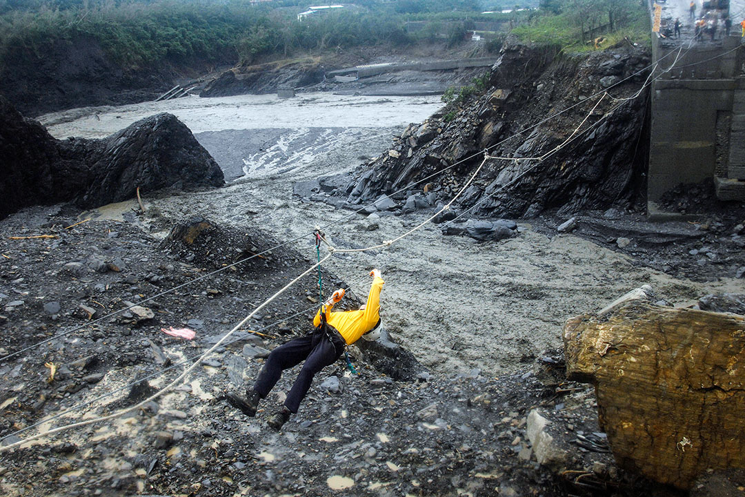2009年8月12日,颱風莫拉克襲台,一名救援人員在高雄縣靠著一條繩索滑過河流。