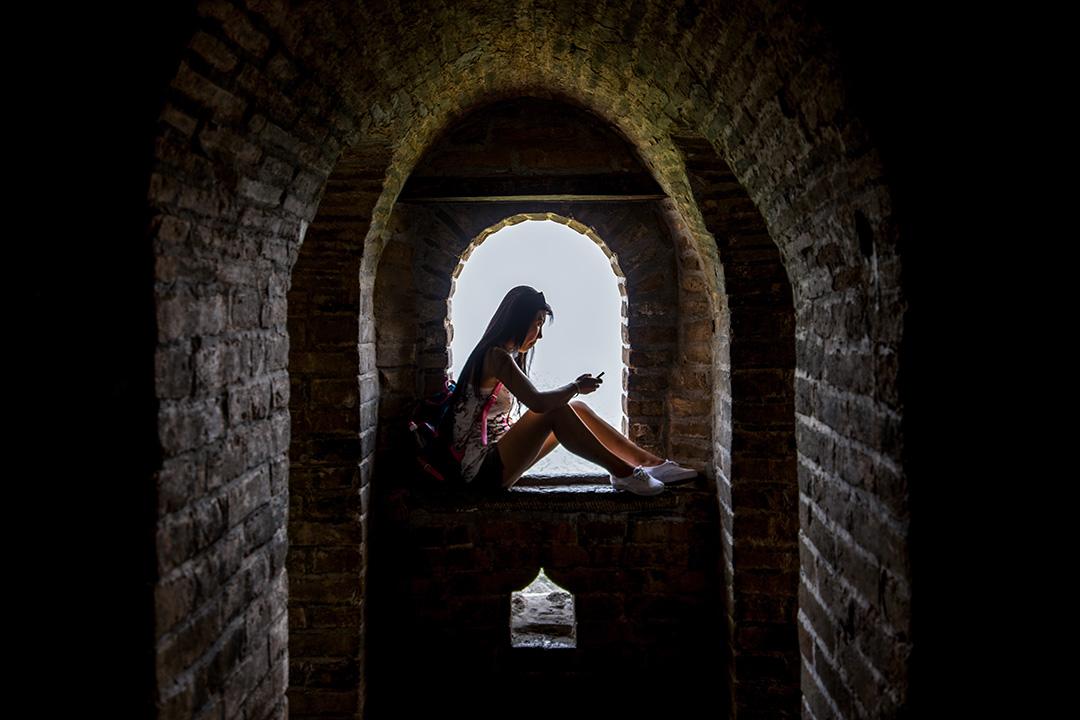 一名女子坐在中國長城裡面的一個窗口看電話。