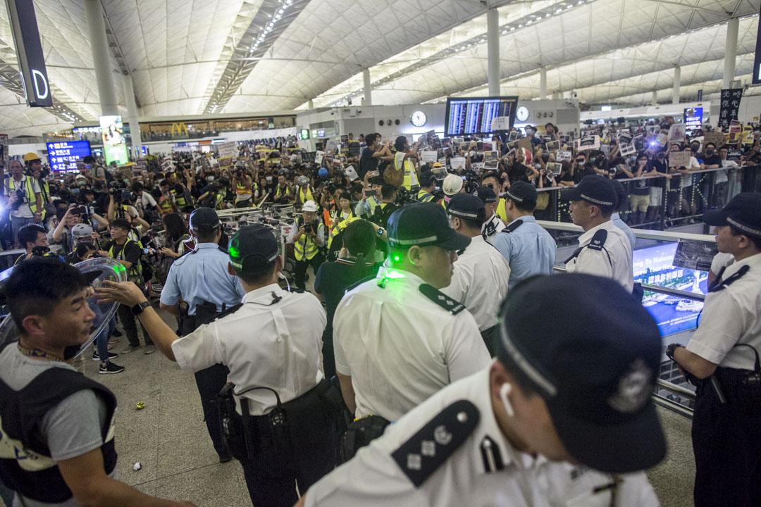 2019年8月13日深夜,示威者聚集機場,有警員到場預備護送傷者離開。