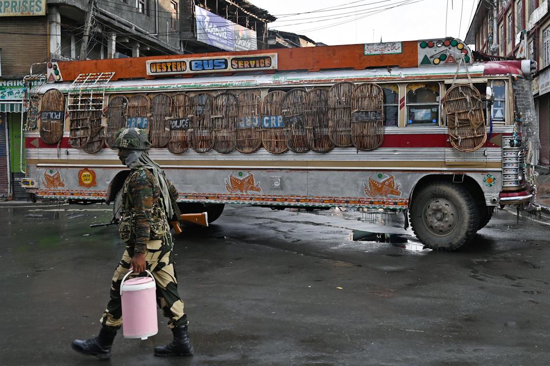 2019年8月8日,一名保安部隊隊員在一輛被示威者用來當路障的巴士前走過。 攝:Tauseef Mustafa/AFP/Getty Images