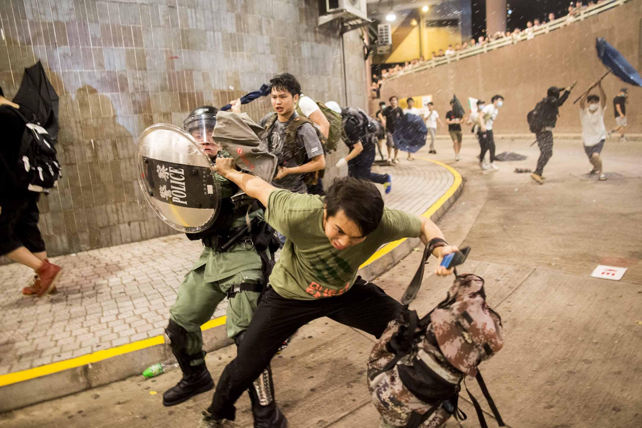 被包圍的警車內警察,突然衝出來以警棍及胡椒噴霧驅散包圍警車的市民。