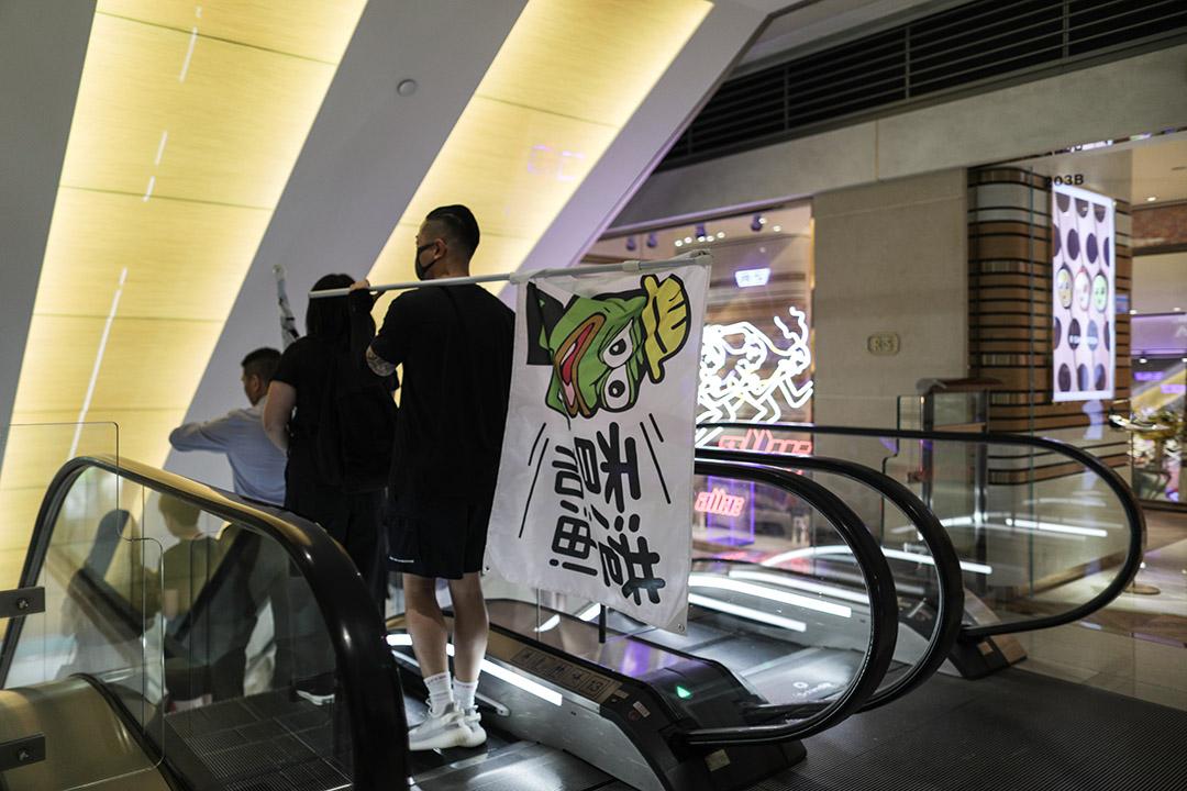 中環商場內,有示威者手持示威版本的「 Pepe」旗幟。