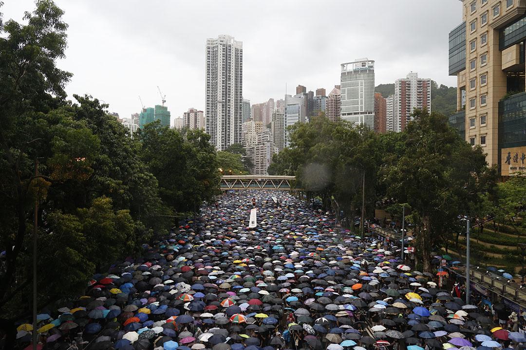8月18日,下午4點多,大批撐着雨傘的示威者經過高士威道