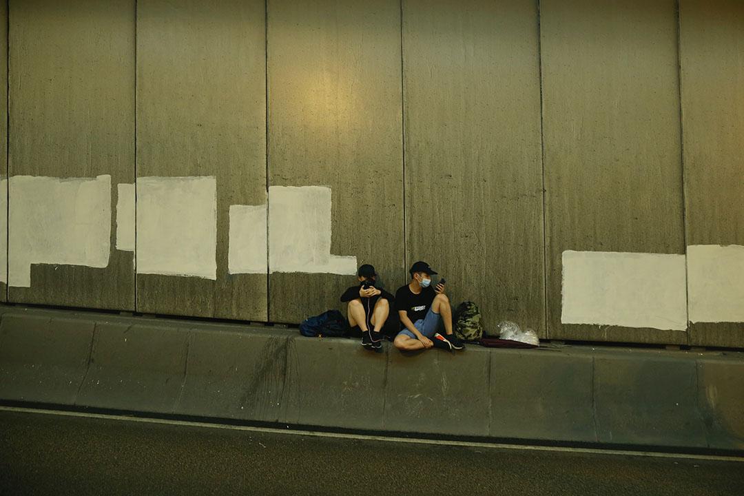 8月18日,7點入夜,在隧道裡休息的兩位年輕示威者。