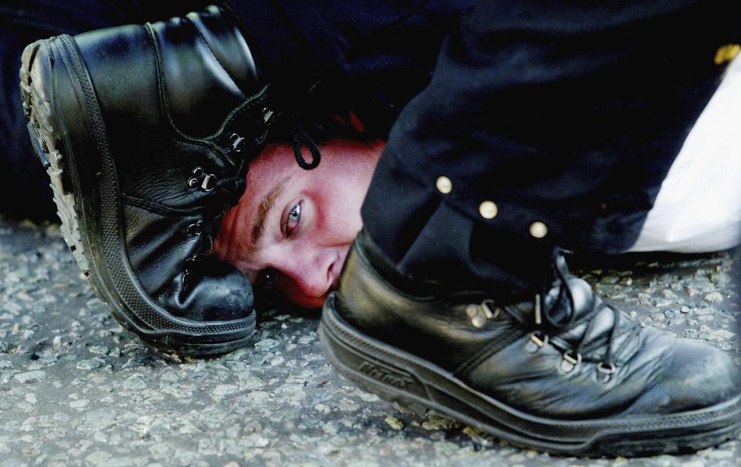 2004年,倫敦一名抗議者被警察制服在地上。 攝:Graeme Robertson/Getty Images