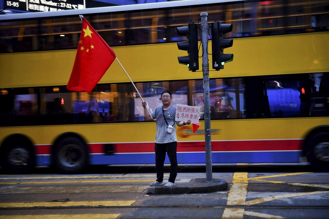 2019年8月26日,一位市民在香港中環揮動中國國旗。