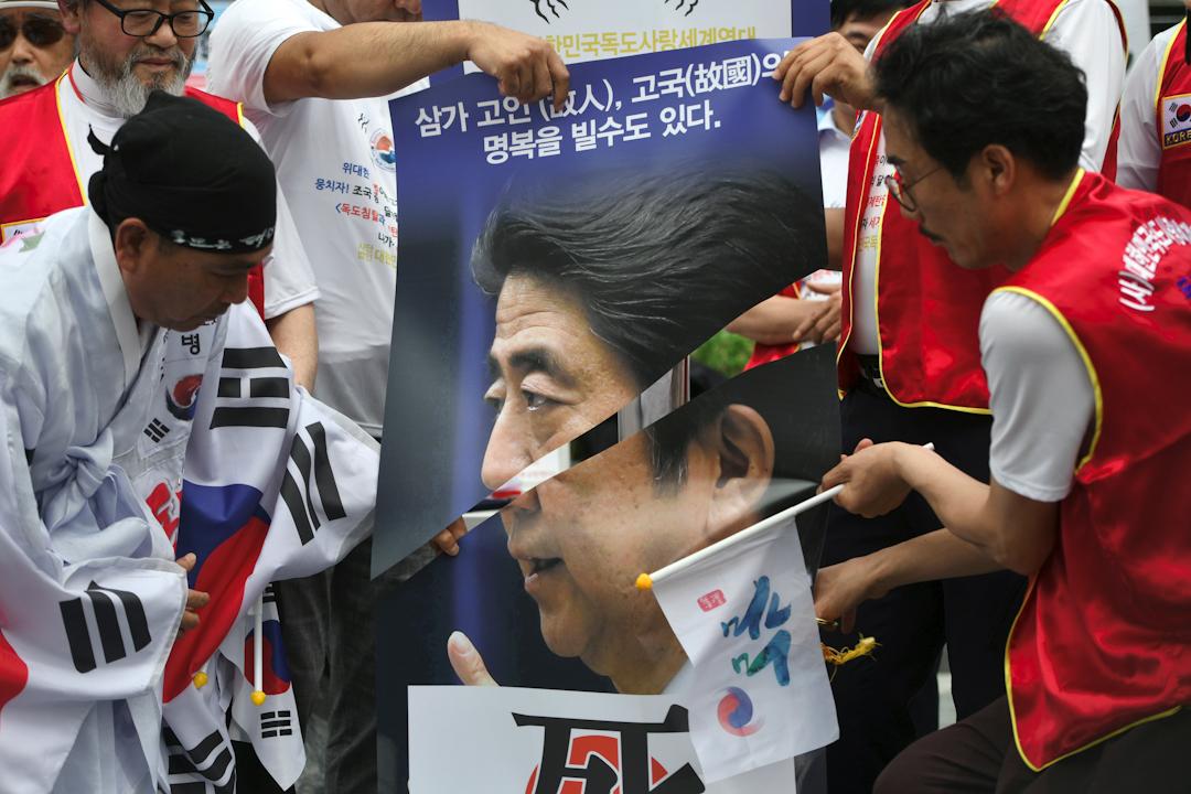 日本安倍內閣決議將韓國從可信賴的貿易夥伴名單中移除,意味著韓國不再享有寬鬆的出口規則。圖為南韓示威者剪爛一幅安倍的肖像,抗議日本對南韓的貿易政策。 攝:Jung Yeon-Je/AFP/Getty Images