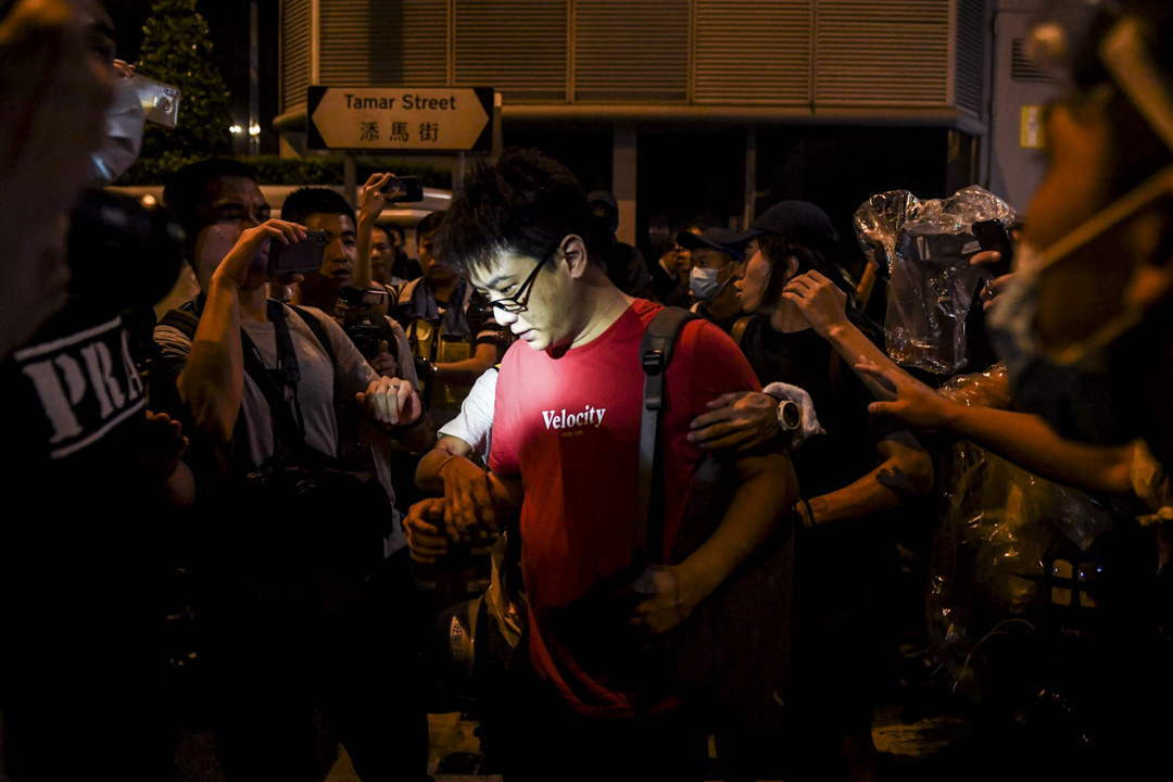 8月18日,現場的示威者於紅衣男子在記者鏡頭前合影。 攝:Lillian Suwanrumpha/AFP/Getty Images