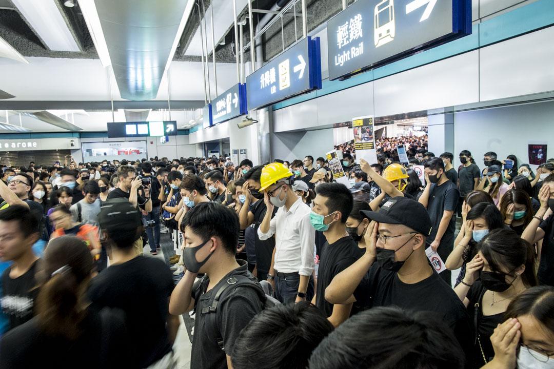 2019年8月21日,香港示威者在元朗站內靜坐,晚上九時正、參與人士全部站立靜默五分鐘,部分人士手掩左眼抗議。 攝:林振東/端傳媒