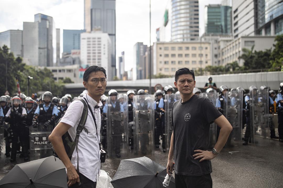 2019年7月1日,示威者在立法會外示威,並佔領馬路,譚文豪(右)在防暴警察前與警方溝通。