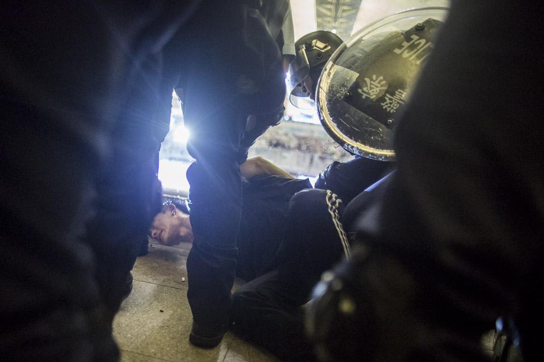 有示威者被警員制止在地上。