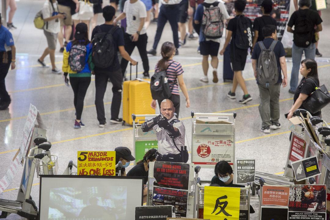 示威者到機場集會,聲討警方濫暴,有參與集會人士展示在葵涌警署外向示威者舉槍的警員的紙板肖像。 攝:林振東/端傳媒