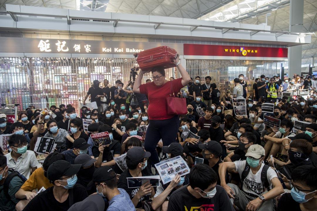 遊客強行穿過示威者人群。