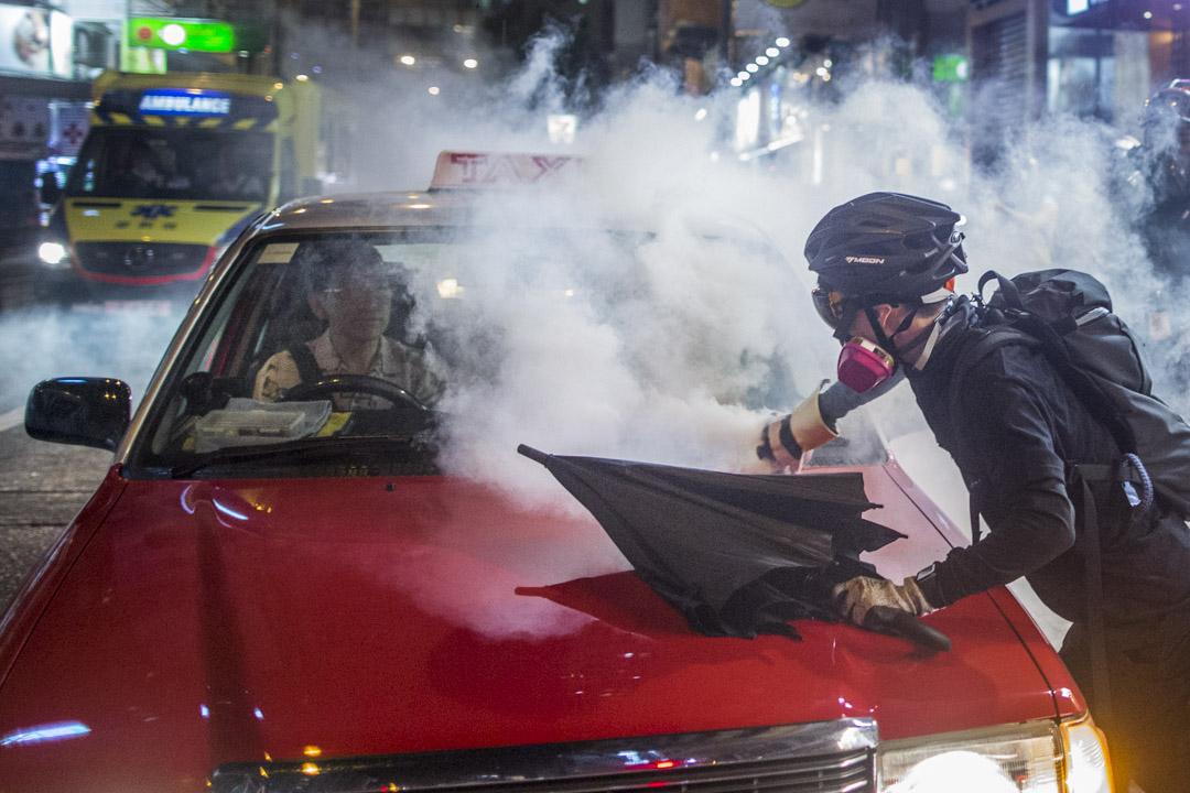 2019年9月29日,示威者拾起射到計程車上的催淚彈。 攝:林振東/端傳媒
