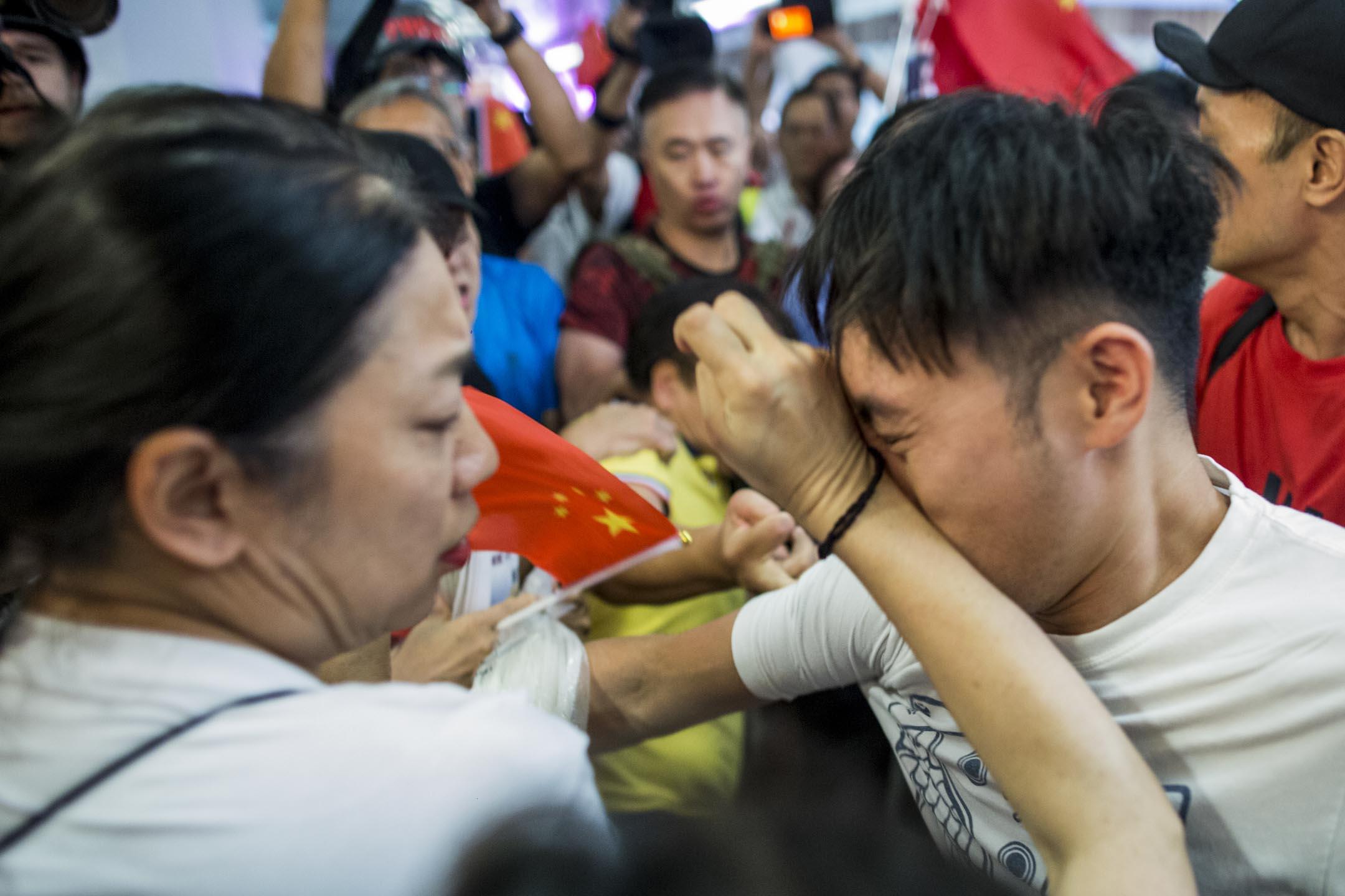 2019年9月14日,九龍灣淘大商場,持國旗的市民與在場一批青年發生口角及打架。 攝:林振東/端傳媒