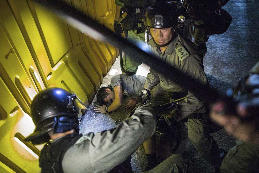 2019年9月16日在香港炮台山,防暴警察制服一名示威者後,向示威者揮舞警棍及噴射胡椒噴霧。 攝:陳焯煇 / 端傳媒