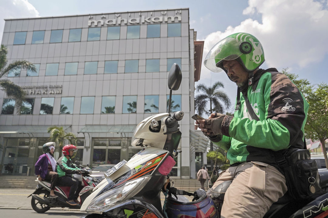 生於印尼本土的Gojek起步於9年前,十年不到就由一個電召摩托車平台變成了一個全方位覆蓋的生活APP——下載數量超過1.4億次,註冊司機超過170萬名,還有成千上萬的商戶也和他們的網絡連接。 攝:Dimas Ardian/Bloomberg via Getty Images