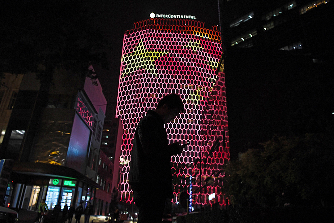2017年10月23日,一名男子在北京一座顯示中國國旗的建築物旁邊看著手機。