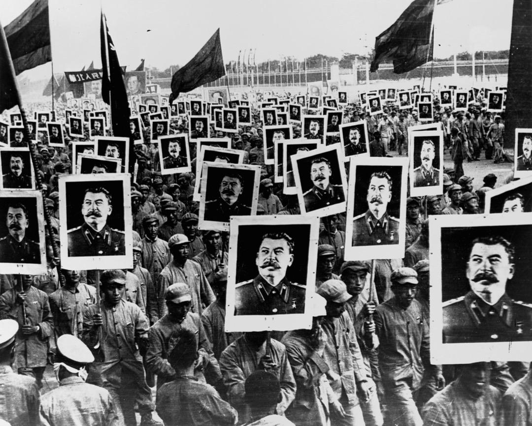 共產極權政權合法化基礎都是脆弱的,它們必須依靠國家的力量才能保證人民的支持,因為它們都是自上而下強行決定的。圖為1951年中國,人們高舉蘇聯總統斯大林的肖像,慶祝共產政權在中國成立一週年。
