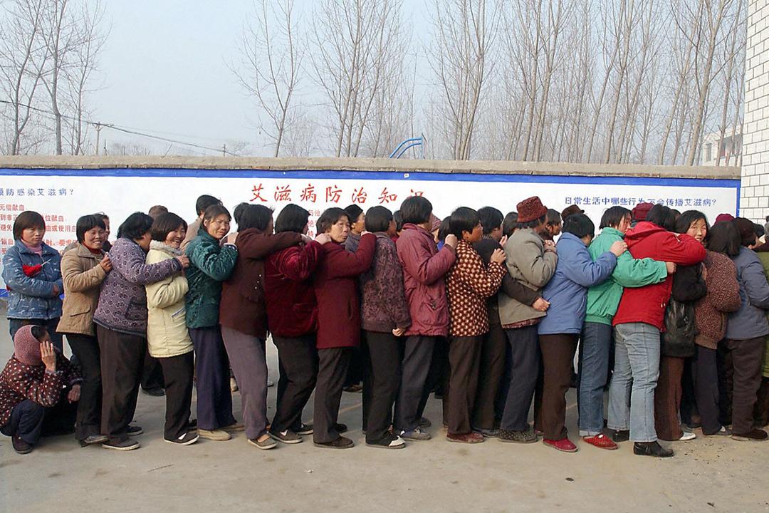 2004年2月21日在河南一條鄉村,農民在診所前排隊,輪候接受免費的 HIV 相關篩查或治療。 圖片來源:STR / AFP / Getty Images