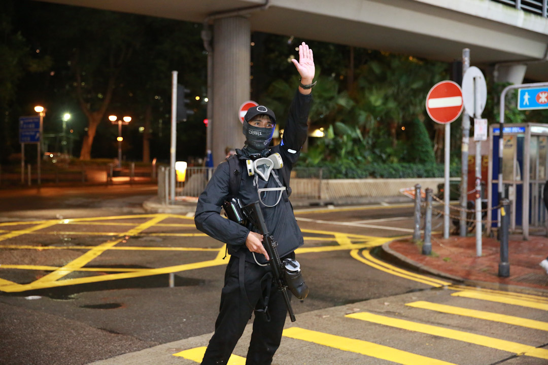 2019年8月31日,在銅鑼灣示威現場,有戴上面罩的人手持由防暴警察使用的胡椒球槍,舉手示意。 圖:端傳媒