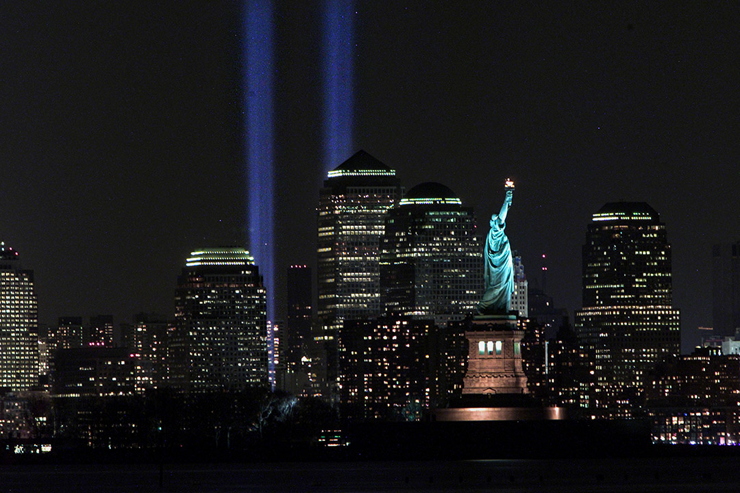 """2002年3月11日,紐約市世貿中心發生恐怖襲擊事件六週年之際,""""光之貢品""""紀念碑閃耀在自由女神像後面。 攝:Don Murray/Getty Images"""