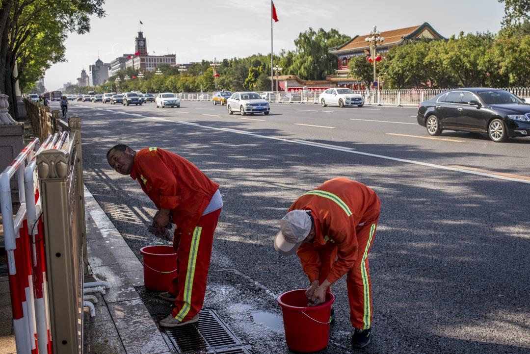 街上有工人提着水桶,擦着街邊金屬色的路障欄。