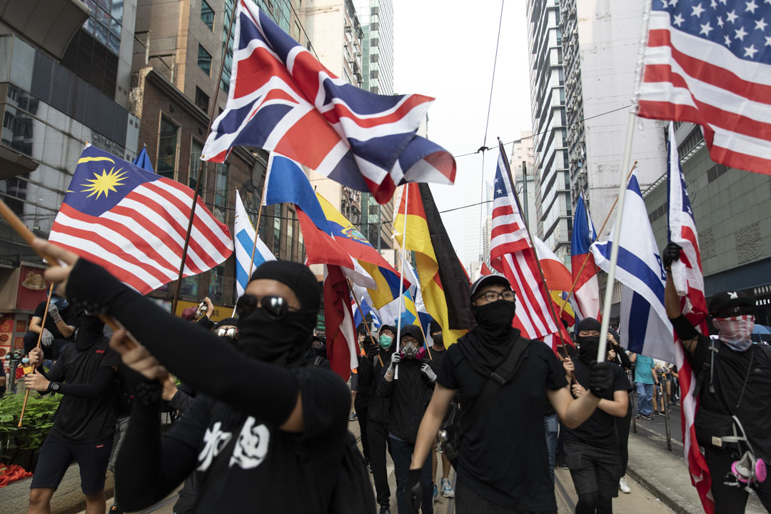 2019年9月29日,香港「反極權大遊行」中有示威者手持多國國旗,感謝全球至少24個國家的65個城市在週末響應聲援香港「反送中」、「反極權」運動。 攝:廖雁雄/端傳媒