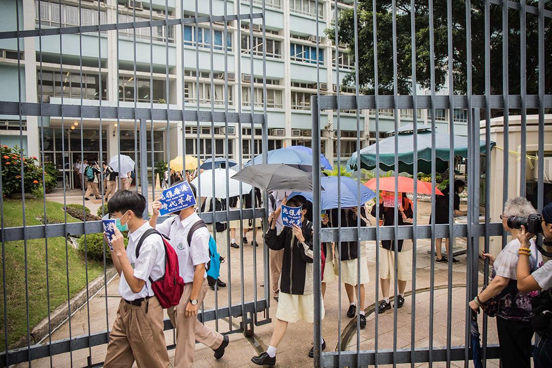 大埔孔教學院大成何郭佩珍中學的學生拿著示威標語步出校園。