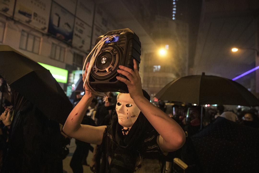 在普遍質疑警方濫捕、律政司作政治檢控之下,參與遊行、示威或抗爭時戴上面具、口罩等已成為「反送中」示威者的常態,建制派近日則大力提倡訂立《禁蒙面法》。圖為2019年9月22日在旺角警署外,一名戴上面具的示威者。 攝:Chris McGrath / Getty Images