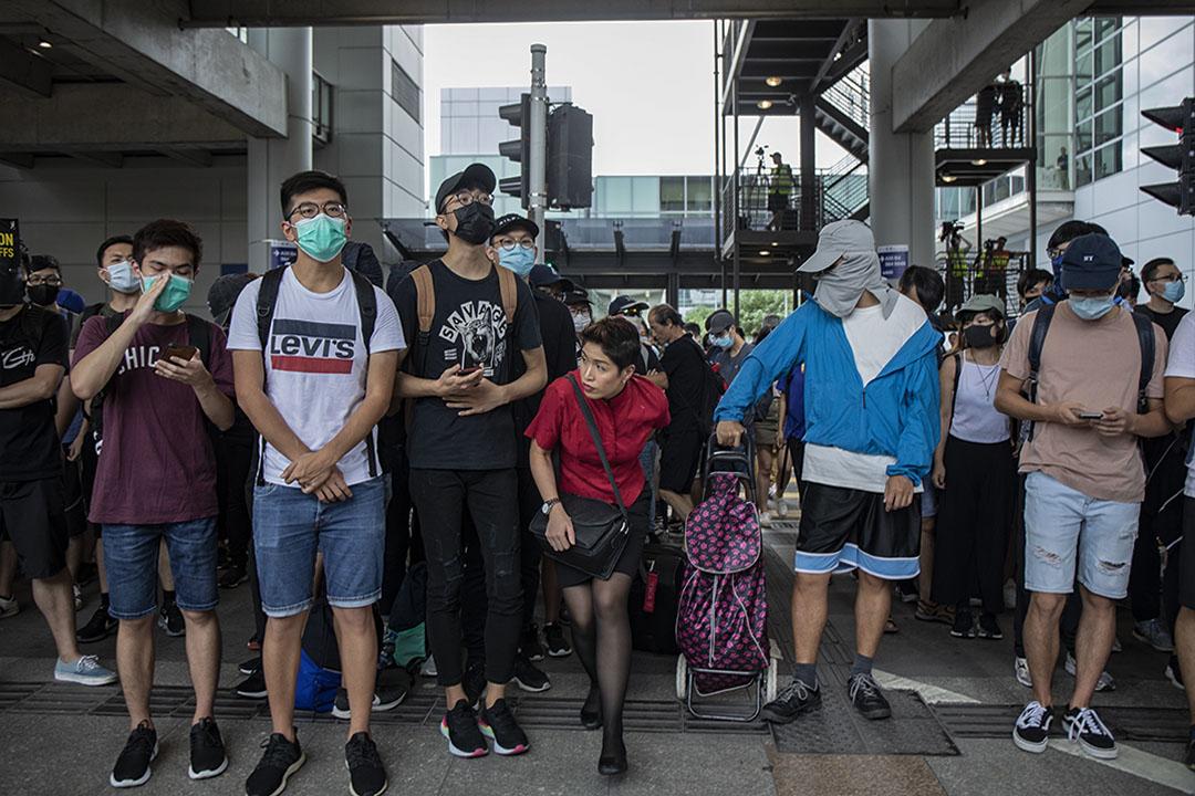 2019年9月1日,示威者包圍機場,意圖癱瘓機場運作,一名空中服務員穿過示威的人群。
