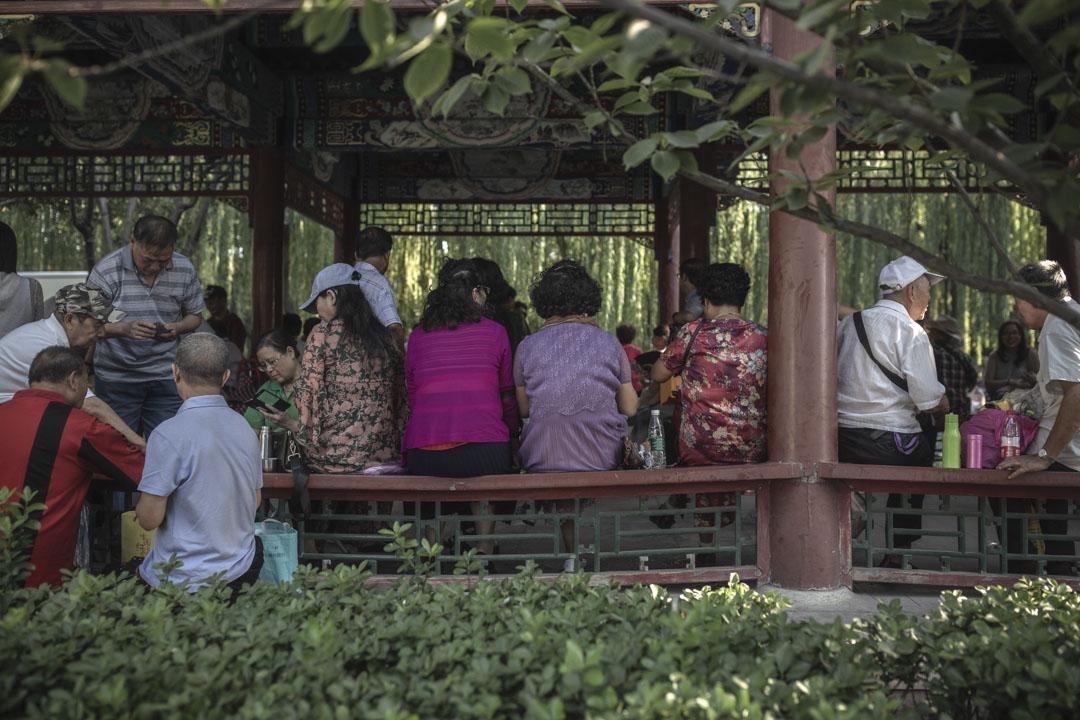 老人們坐在公園長廊裏相互搭訕。